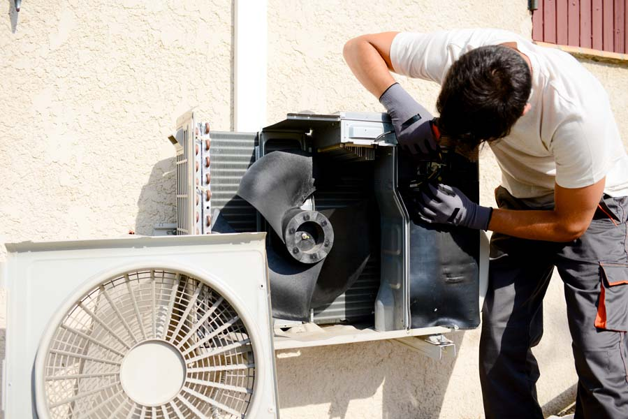 young man electrician installer working on outdoor compressor unit air conditioner in Petal