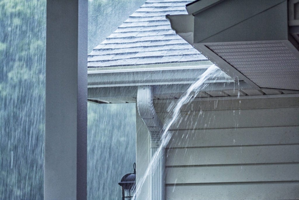 Rain storm water is gushing and splashing off the tile shingle roof pouring over the overhanging eaves trough aluminum roof gutter system on a suburban residential colonial style house near Rochester