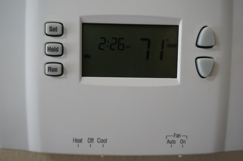 white thermostat hanging on a beige wall
