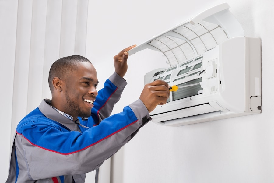 HVAC technician fixing a ductless air conditioning unit in Petal
