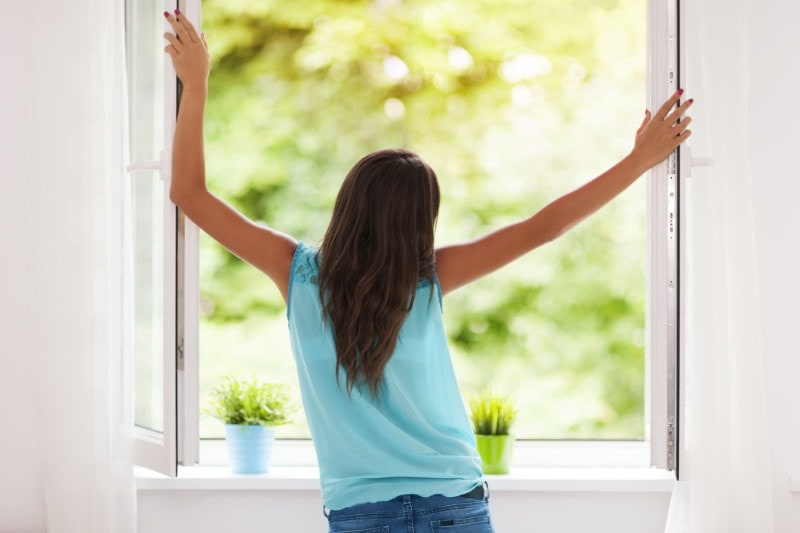 Girl standing in summer window.
