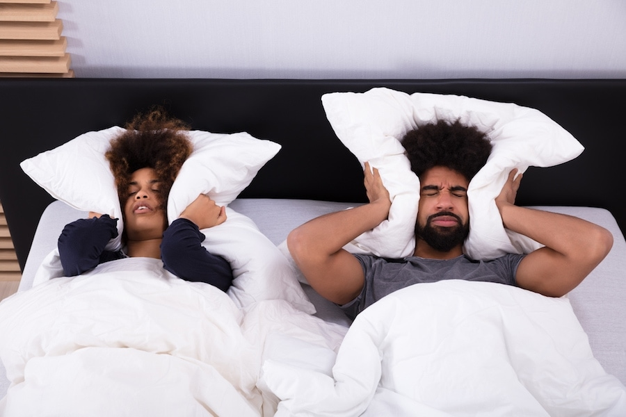 Elevated View Of Young Couple Lying In Bed Covering Their Ears With Pillow