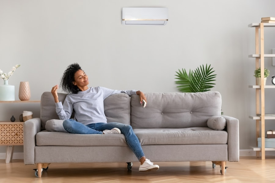 Beautiful black woman on a couch relaxing in her home with clean indoor air in Petal