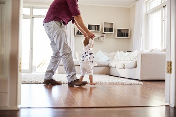 Man walks with baby holding his hands as he teaches the baby to walk in a comfortable home.