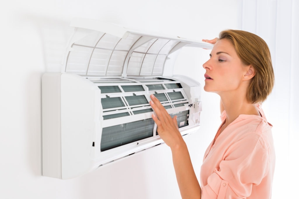 Woman looking at air conditioner