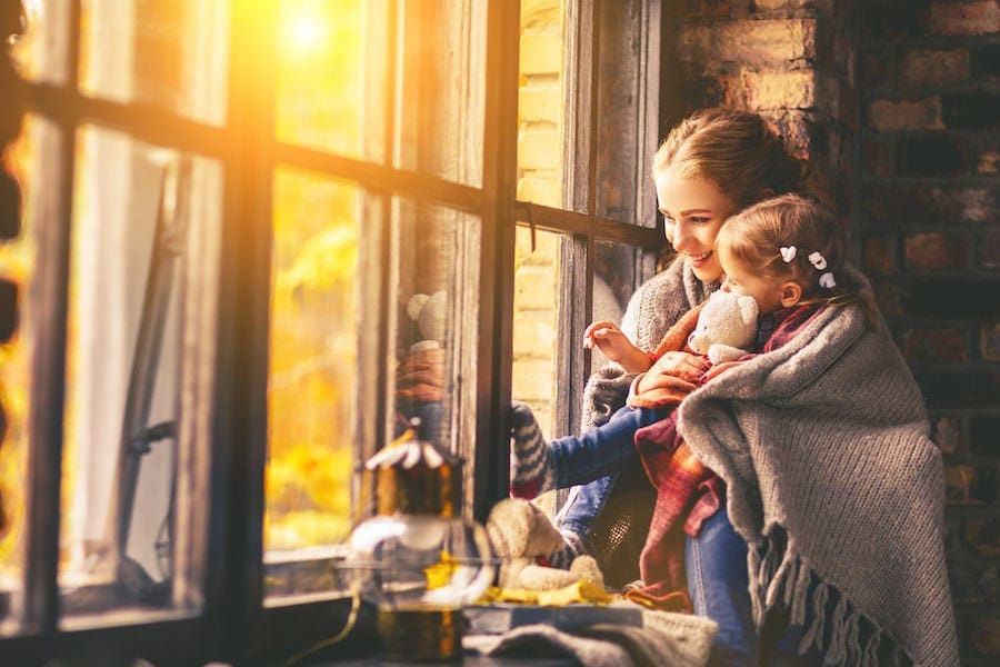 Woman and child by a sunny window wrapped in a blanket.